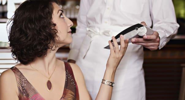 Woman paying waiter at restaurant