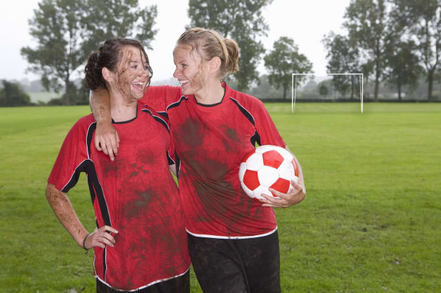 Muddy teenage girls laughing and holding football on field