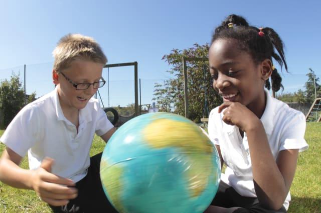 school children looking at globe