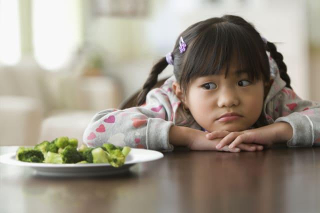 Girl looking at broccoli