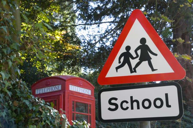 School crossing sign, telephone box in background