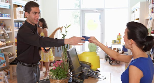 Man Giving Credit Card to Cashier