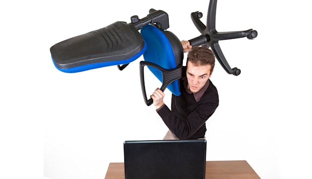 young angry man standing above a laptop with an office chair preparing to destroy it
