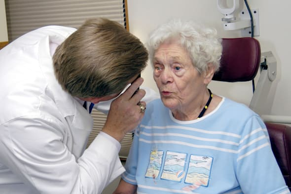 Senior female undergoes eye examination by an optometrist