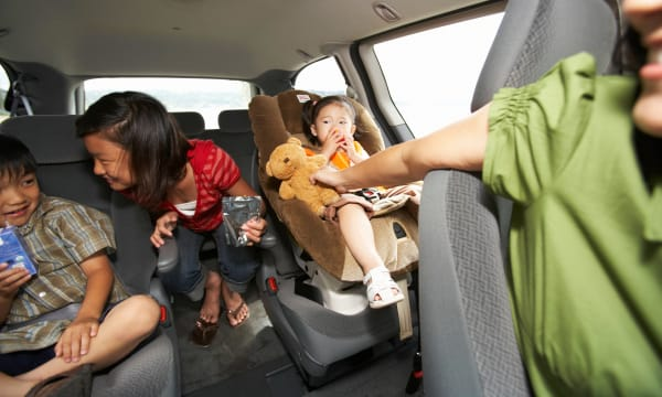 Mother handing toy to children (1-10) travelling in car