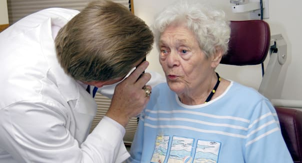 Senior female undergoes eye examination by an optometrist