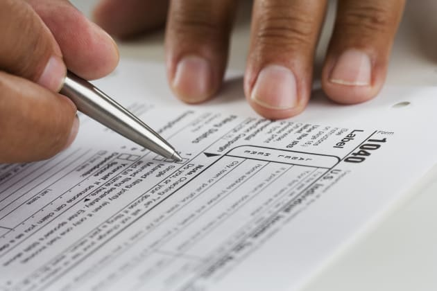 Close up of hands filling in tax form