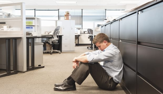Business man sitting on floor of office