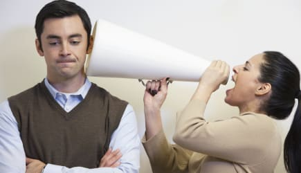 Businesswoman shouting with megaphone into co-worker's ear
