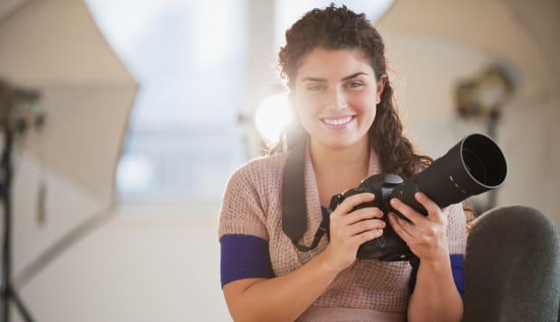 Mixed race woman holding camera