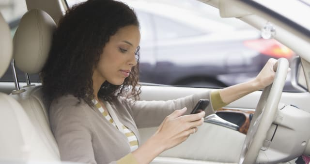 Woman checking phone in car