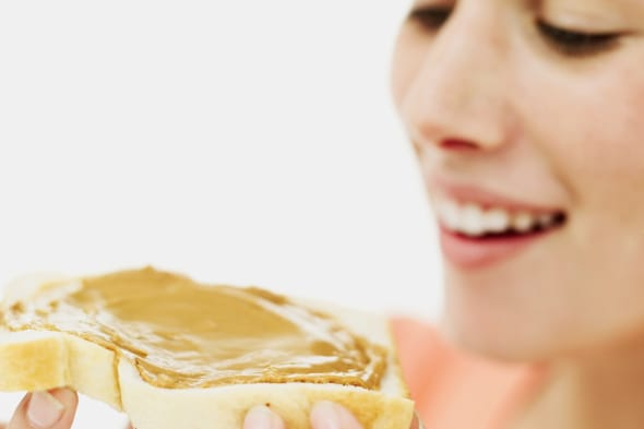 close-up of a teenage girl holding a slice of bread with peanut butter