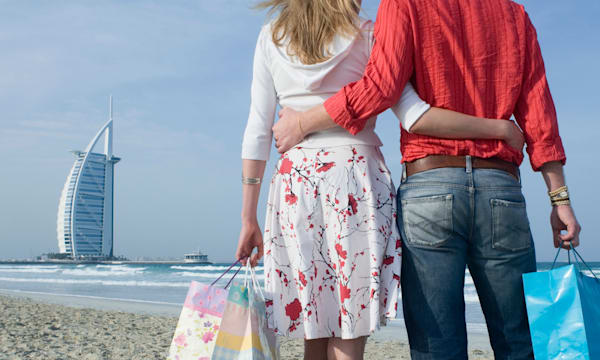 Couple on the beach with shopping bags, Dubai, United Arab Emirates