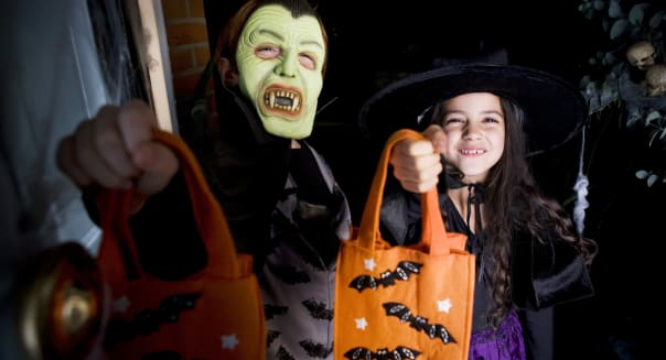 Children in costumes at a Hallowe'en party, holding orange party bags