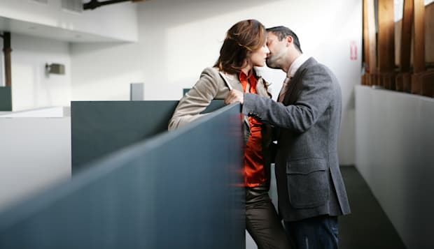 Two people kissing in the office