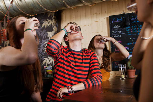 Young friends drinking from shot glass in bar