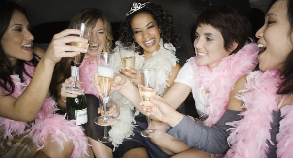 Multi-ethnic bachelorette party toasting with champagne