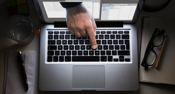 Hand appearing from laptop screen touches keyboard