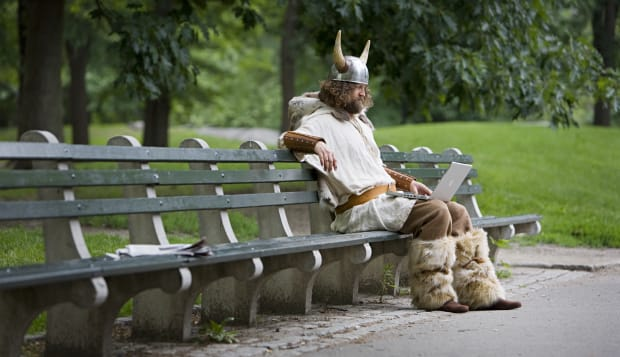 Viking sitting on bench with laptop.