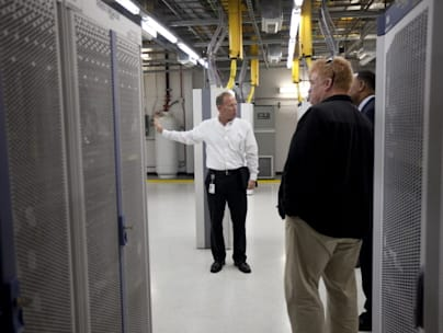 CHARLOTTE, NC  - OCTOBER 25:  An AT&T employee (Left) gives a tour of the mobile telephone switching office to local officials on October 25, 2012 in Charlotte, North Carolina.  The center handles wireless AT&T traffic from the western part of North Carolina. (Photo by John W. Adkisson/Getty Images)