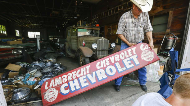 In this Aug. 12, 2013 photo, Art Nordstrom holds a sign at the former Lambrecht Chevrolet car dealership in Pierce, Neb. In September, bidders from at least a dozen countries and all 50 U.S. states will converge on Pierce, a town of about 1,800 in northeast Nebraska, for a two-day auction that will feature about 500 old cars and trucks, mostly Chevrolets that went unsold during the dealership?s five decades in business. About 50 have fewer than 20 miles on the odometer, and some are so rare that no one has established a price. The most valuable could fetch six-figure bids. (AP Photo/Nati Harnik)