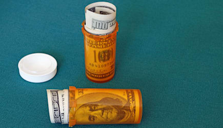 Symbolic presentation of the high cost of prescription medication. US $100 bills in pill containers.