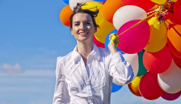 businesswoman holding bunch of balloons