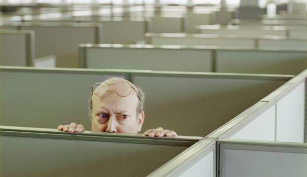 Older man hiding behind office cubicle