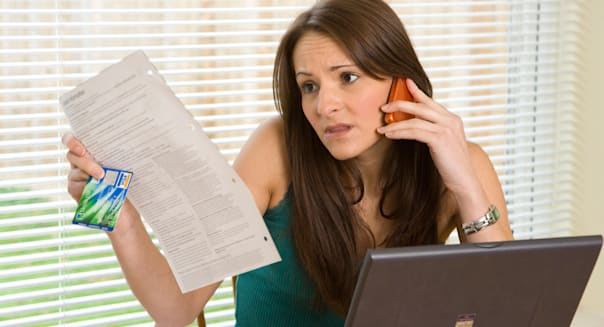 worried woman on phone checking  credit card / bank statement / bills