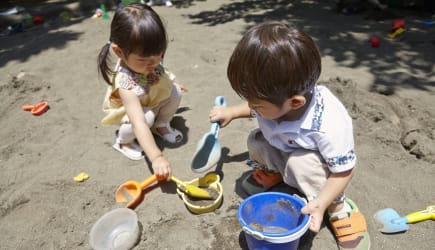 Two children who play in a sandbox.