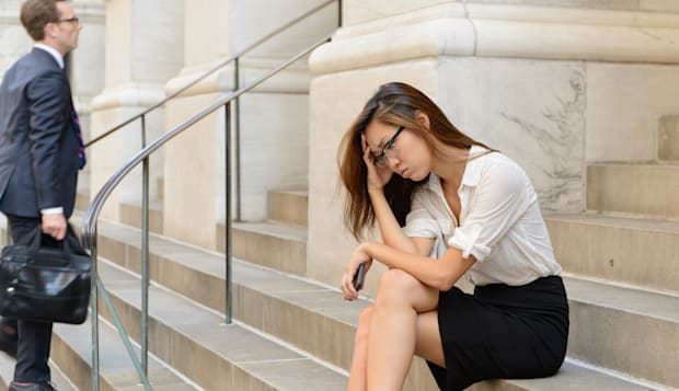Business woman on steps looking worried