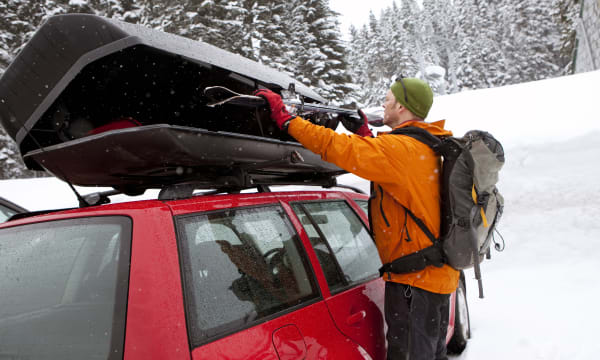 A man loading skis on top of a car.