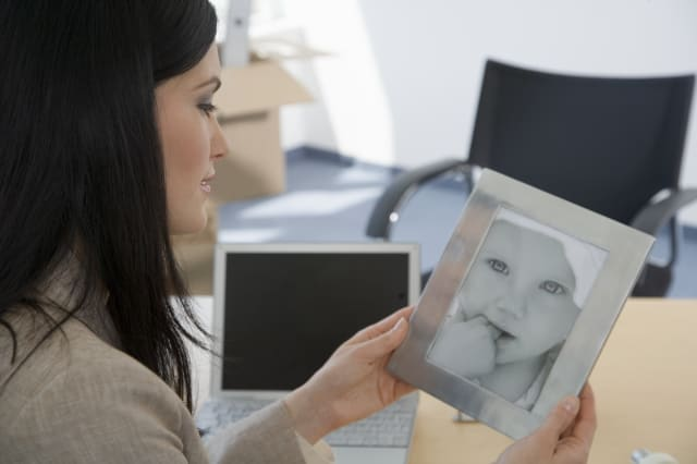 Businesswoman looking at photograph of baby on desk