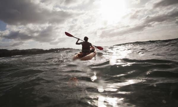 Silhouette of a young man paddling out to sea in a kayak