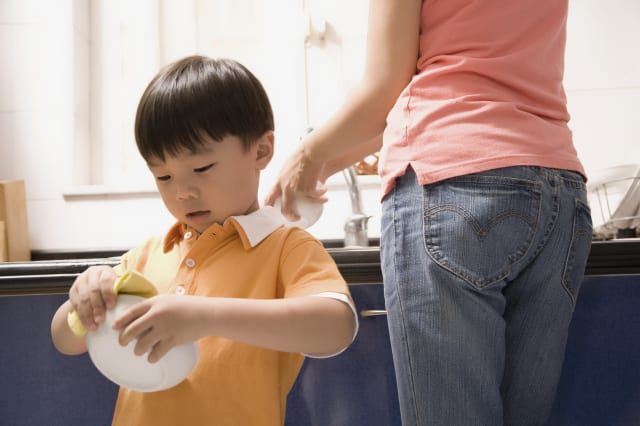 Boy helping his mother in the kitchen
