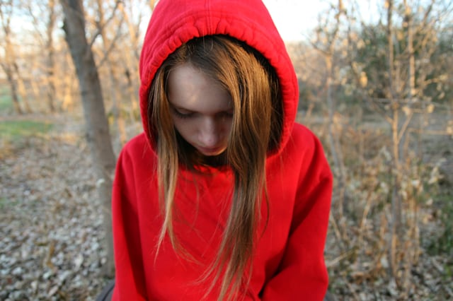 Teenage girl wearing a red hoodie looking down, Brooklyn Park, Minnesota