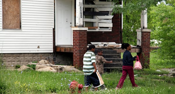 Mother and two sons walking past boarded up house in Detroit