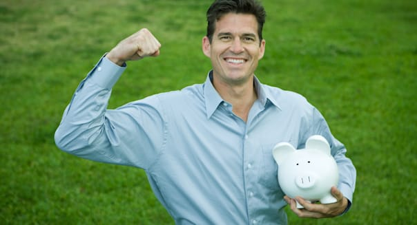 Man holding piggy bank, raising fist and smiling at camera