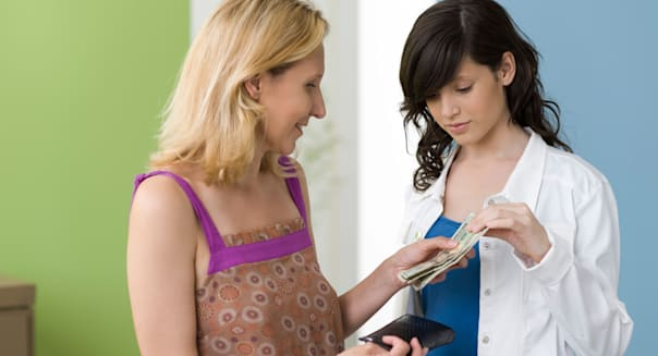 Mother giving teenage daughter pocket money