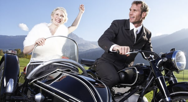 Bride and groom riding motorcycle with sidecar in rural area