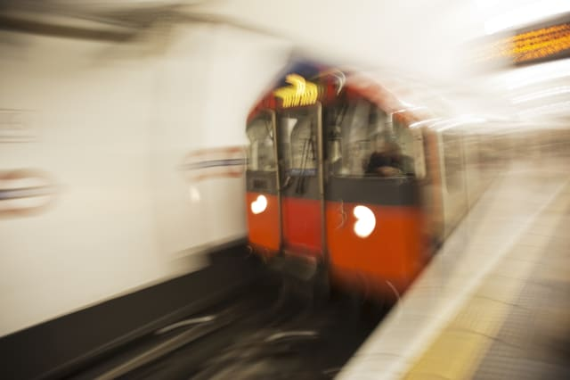 A London Underground train enters a station.