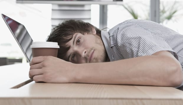 Germany, Cologne, Young man lying on table with laptop and cup, close-up