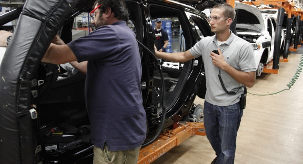 Autos More Jobs (In this Wednesday, May 8, 2013, photo, Jeff Caldwell, 29, right, a chassis assembly line supervisor, watches an