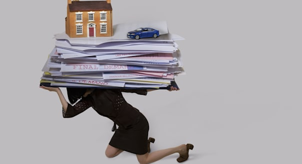 woman carrying a stack of bills, house and a car