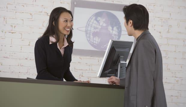 Businessman talking to businesswoman behind receptionist desk