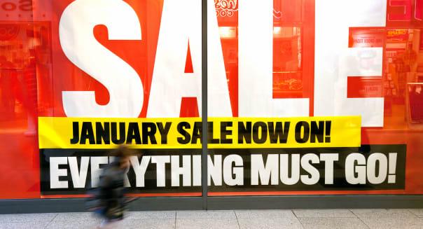 January Sale UK sign shop window and child running, Lion Yard, Cambridge England