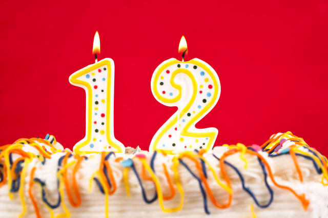 Decorated birthday cake with number 12 burning candles. Red background.