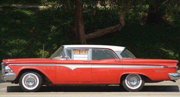 Red old American car 1970?s 1960?s parked for sale gas guzzler fuel price