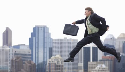 Businessman jumping over city