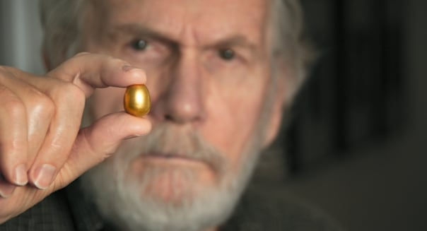 conceptual image of man holding a small gold egg